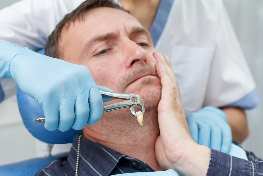 a dentist performing tooth extraction treatment on a patient